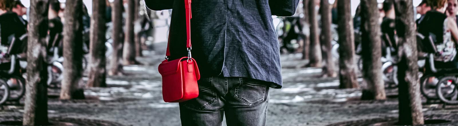 Ein Mann trägt eine Handtasche über die Schulter