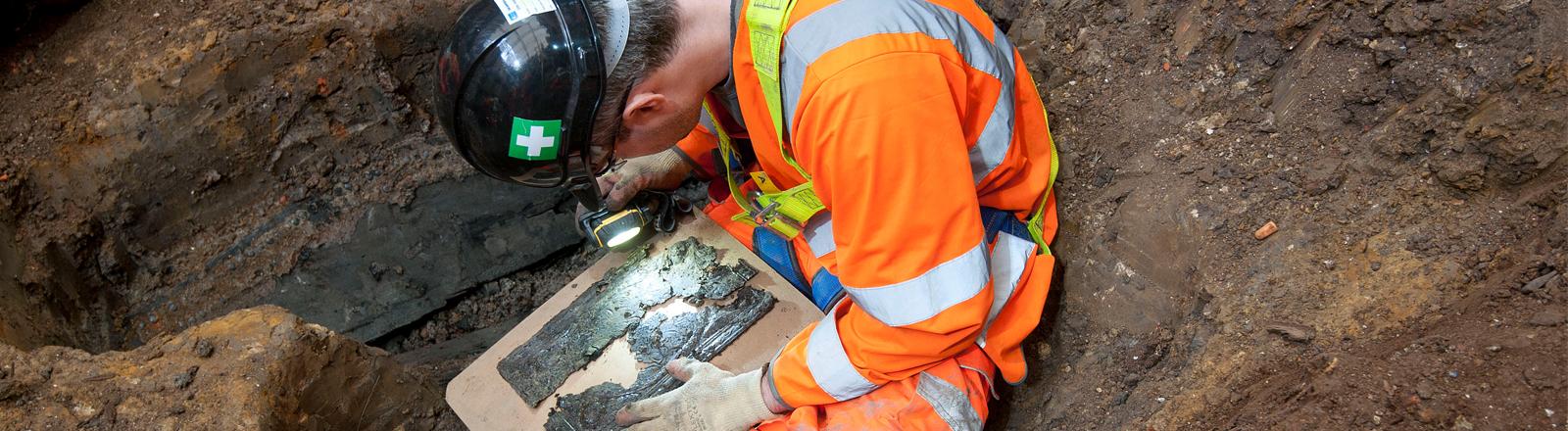 Ein Archäologe untersucht ein ausgegrabenes Sarg auf einem Londoner Friedhof