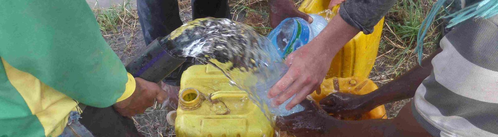 Aus einem Rohr strömt das erste Wasser des Brunnens in Kanister.