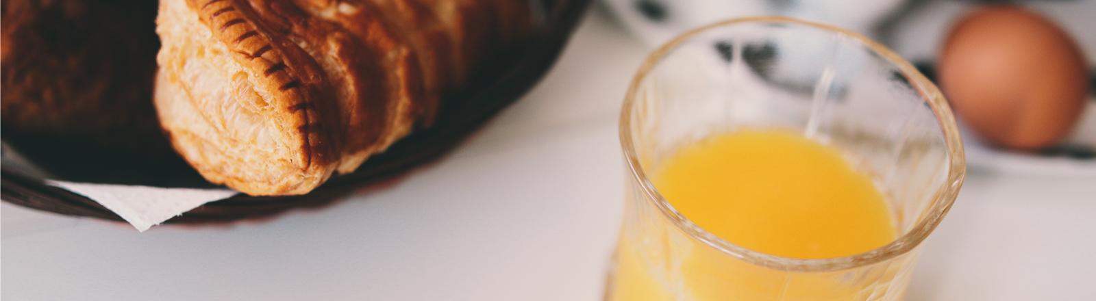Eier, Croissant, Orangensaft auf Frühstückstisch