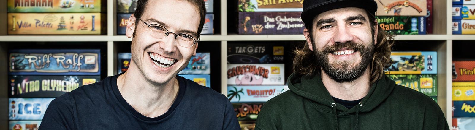 Zwei Männer sitzen vor einem Regal mit Brettspielen und lachen in die Kamera.