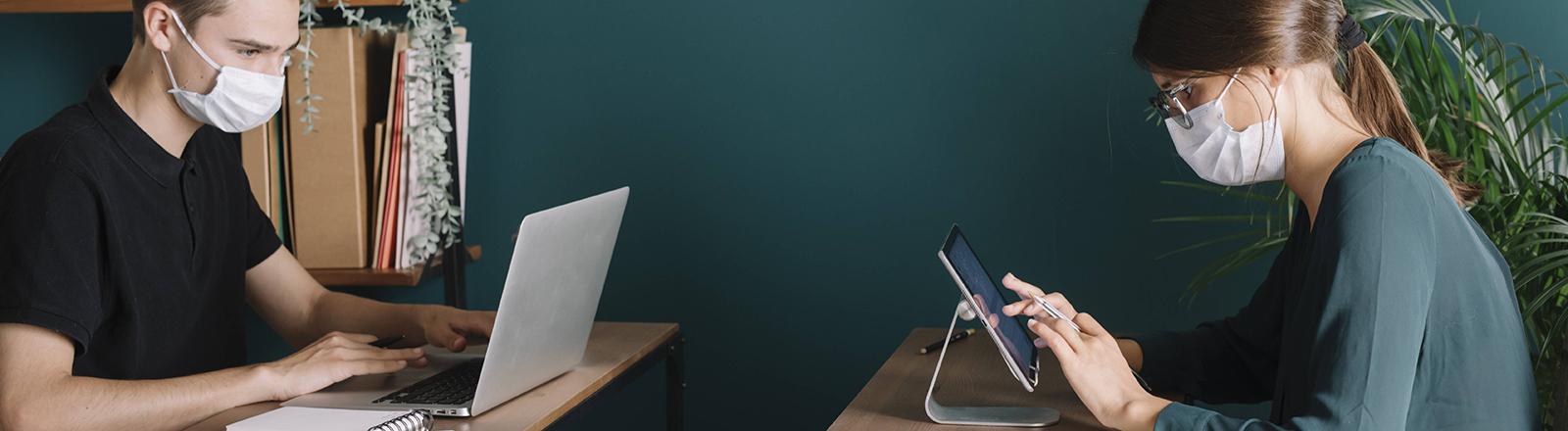 Zwei Menschen arbeiten an ihren Laptops und sitzen sich gegenüber, dabei tragen sie Masken.