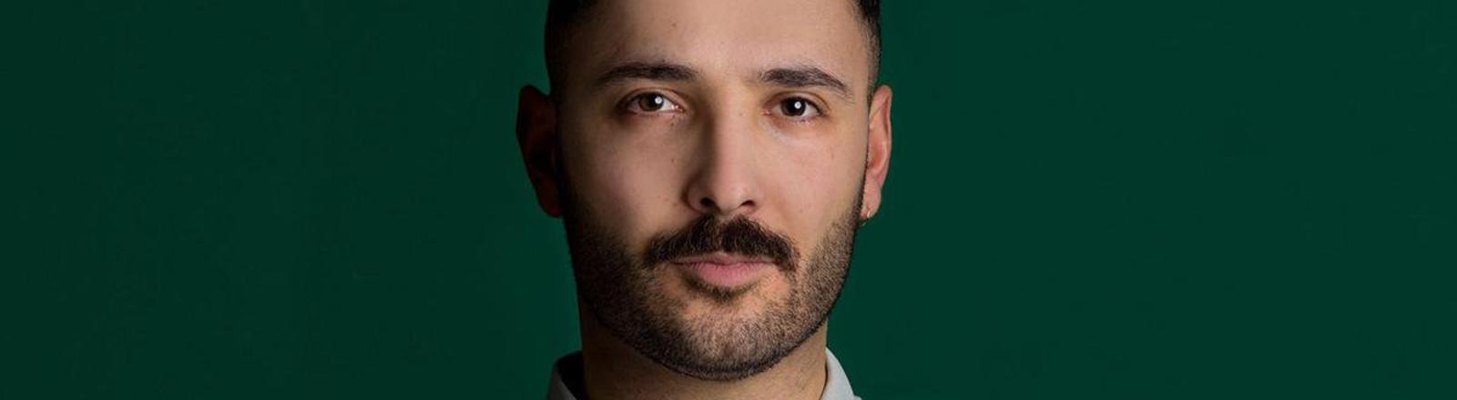 Close up von einem Mann im Poloshirt vor grünem Hintergrund.