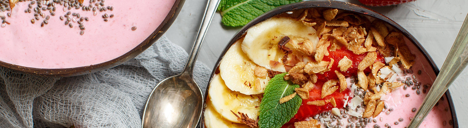 Zwei Schüsseln mit Yoghurt stehen nebeneinander, sie sind mit Früchten und Körnern dekoriert.
