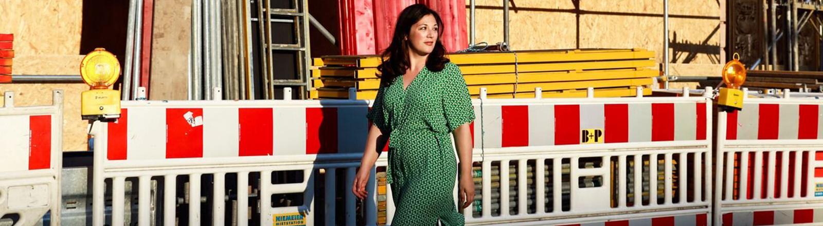 Eine Frau geht in einem grünen Kleid an einer Baustelle vorbei und schaut nach hinten.