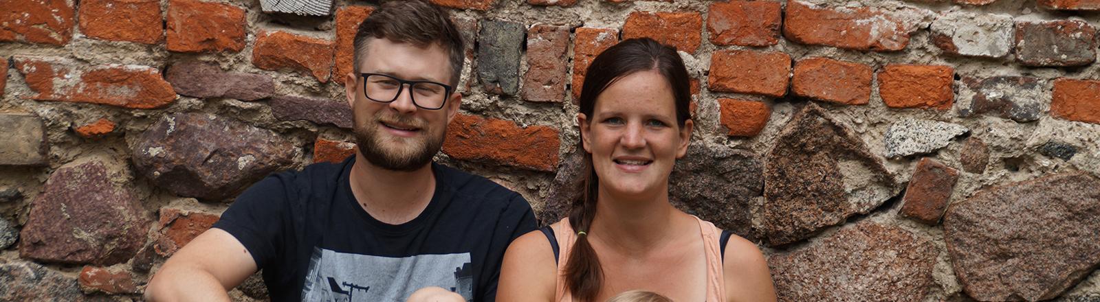 Eine Frau und ein Mann sitzen mit zwei Kindern auf dem Boden vor einer Backsteinmauer.