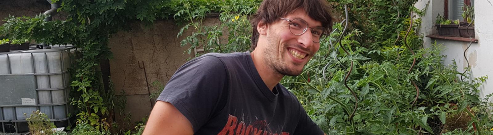 Ein Mann steht vor Tomatenpflanzen und schaut lächelnd in die Kamera.