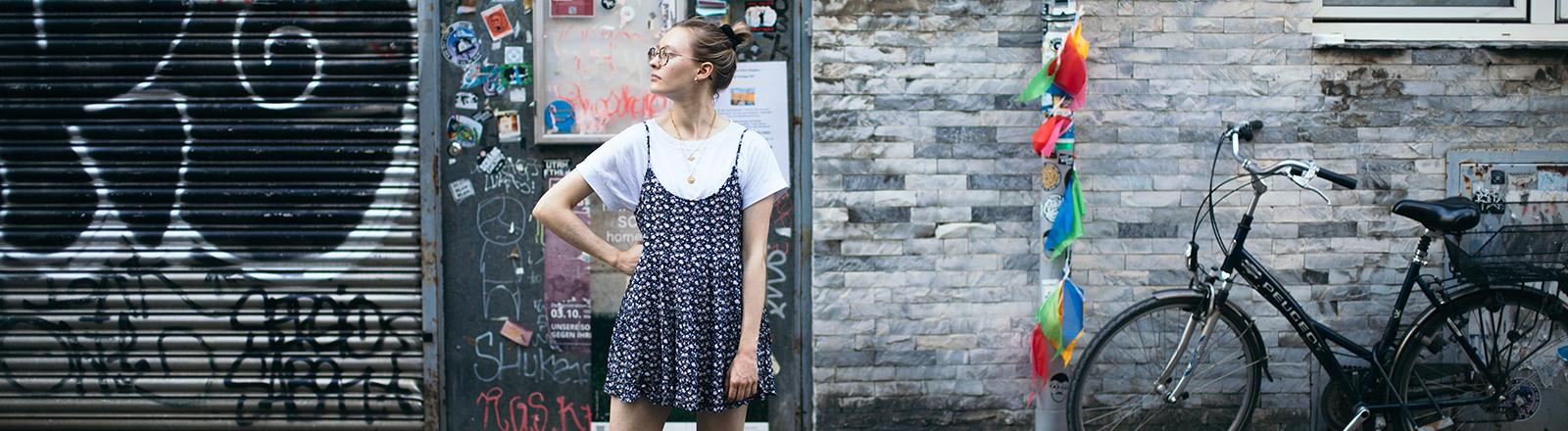 Eine Frau steht vor einer beklebten Tür auf einer Straße.