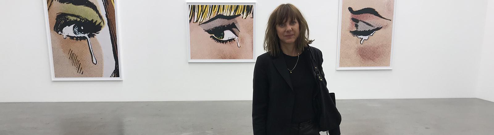 Eine Frau steht im Vordergrund, im Hintergrund hängen drei Gemälde an der Wand.