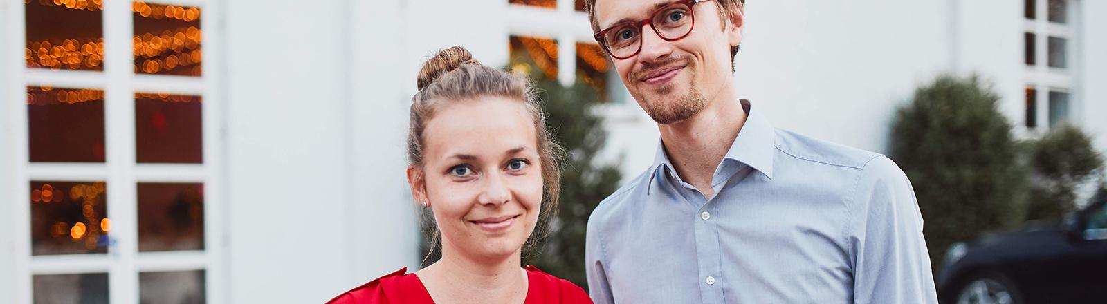 Eine Frau schaut lächelnd in die Kamera, ein Mann mit Brille steht daneben und hält ein Bierglas in der Hand.