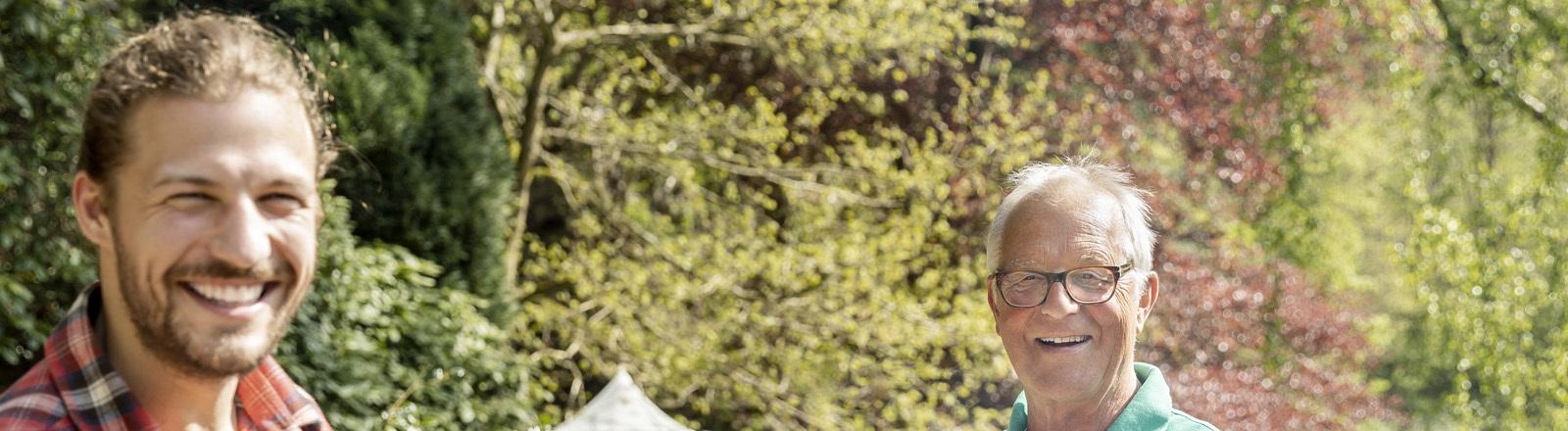 Ein junger Mann hält mit einer Grillzange eine Bratwurst hoch, dahinter steht ein älterer Mann mit einer Grillplatte.