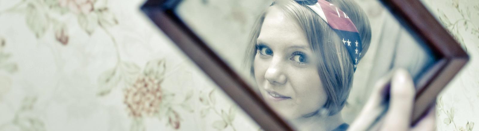Eine junge Frau schaut in einen Spiegel.