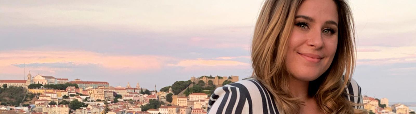 Eine Frau schaut in die Kamera, hinter ihr ist eine Stadt im Sonnenuntergang zu sehen.