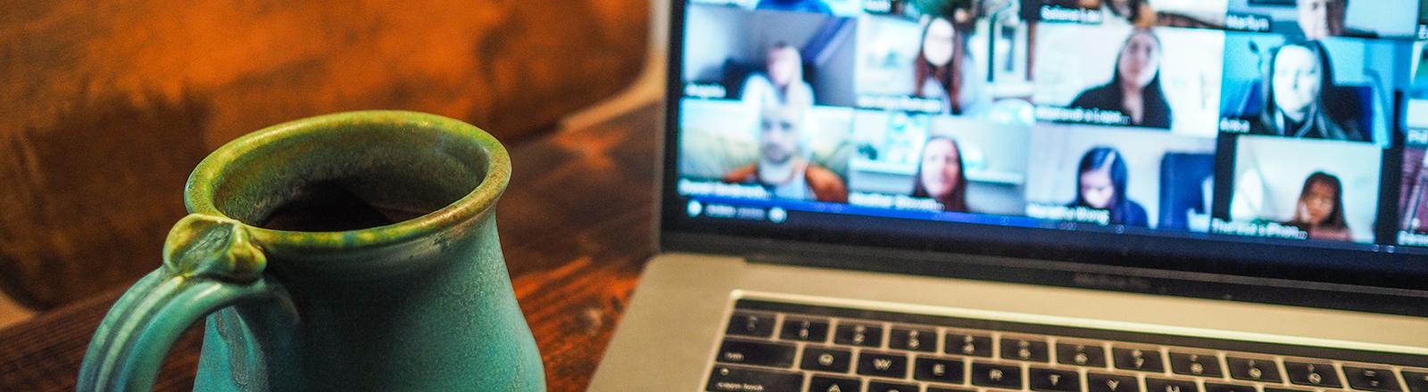 Eine Tasse steht neben einem Laptop, auf dessen Bildschirm sind viele verschiedene Gesichter in einem Videocall zu sehen.
