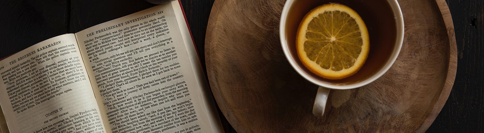 Auf einem Tisch liegt ein aufgeschlagenes Buch, daneben steht eine Tasse Tee mit einer Orangenscheibe.