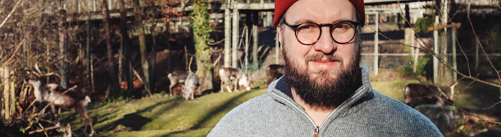 Ein Mann mit Mütze und Brille steht vor einem Gehege mit Renntieren.