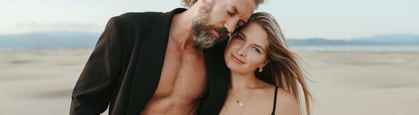 Ein Mann mit nackter Brust und offenem Jacket steht neben einer Frau an einem Strand.