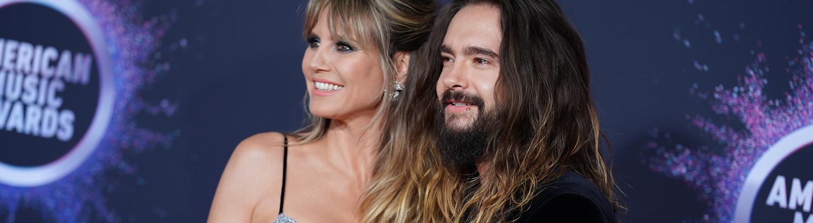 Ein Mann und Frau stehen vor einem bunten Hintergrund und schauen links in die Kamera.