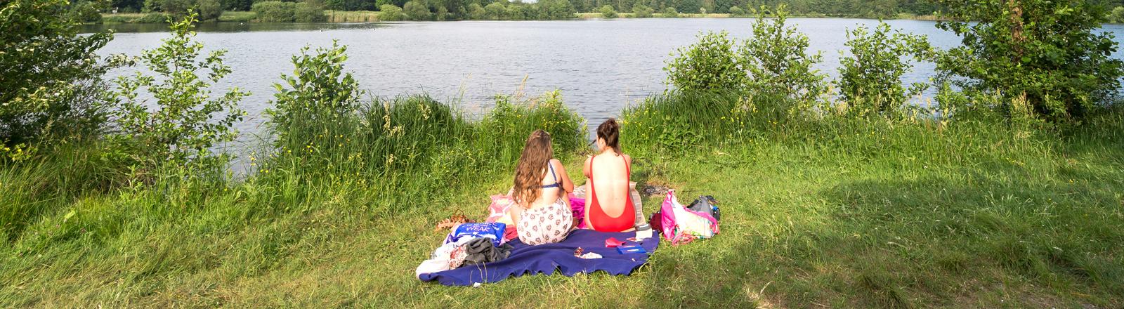 Zwei Frauen in Badeanzügen an einem See.