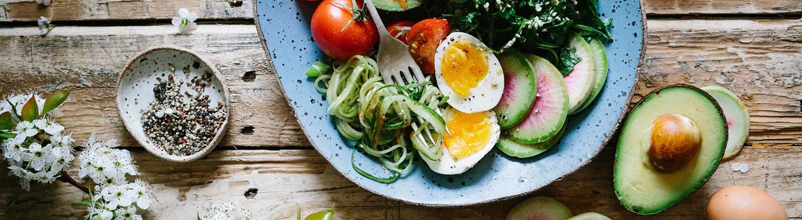 Ein Teller mit frischem Gemüse und Ei steht auf einem Tisch.