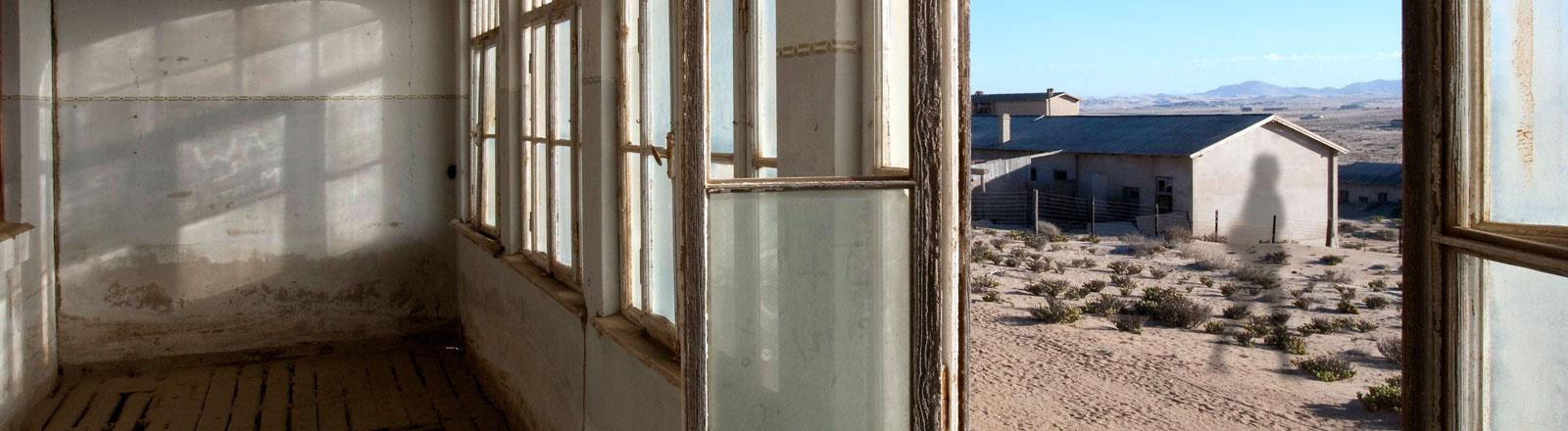 Ein leerer Raum mit einem geöffneten Fenster - draußen geht ein schemenhafter Schatten vorbei.