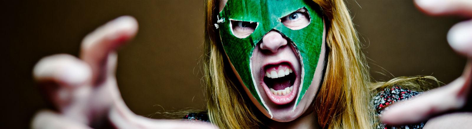 Eine junge Frau mit selbstgebastelter Maske versucht sich im Wrestling.