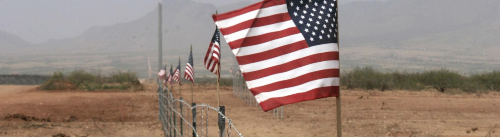 Ein Stacheldrahtzaun mit amerikanischen Flaggen auf den Pfählen. Bild: dpa