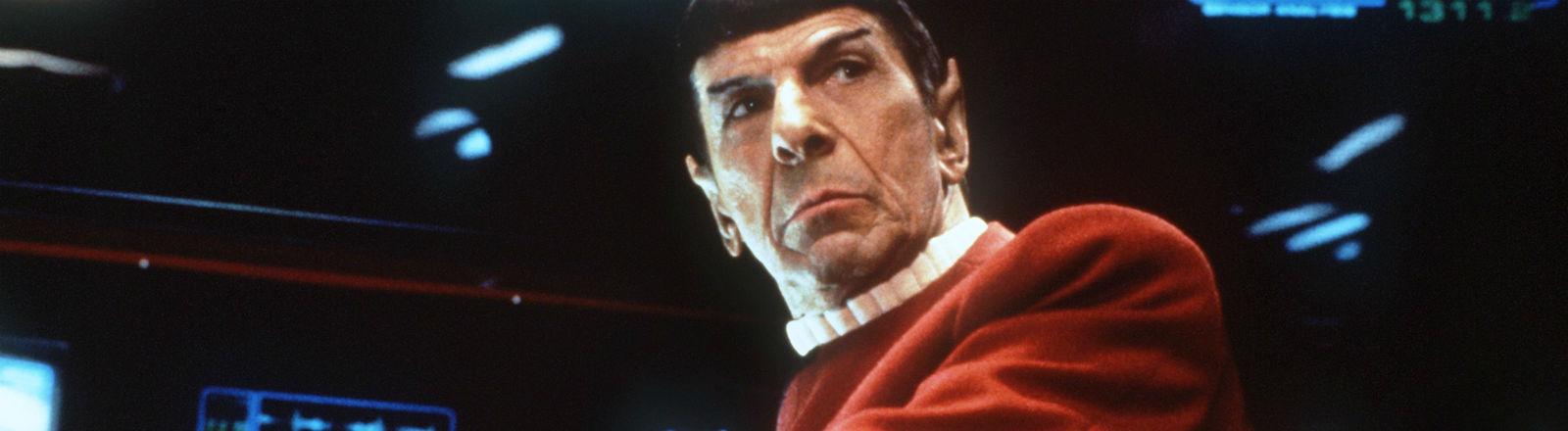 Ein Mann mittleren Alters mit spitzen Ohren sitzt in einem Raumschiff. Bild: dpa