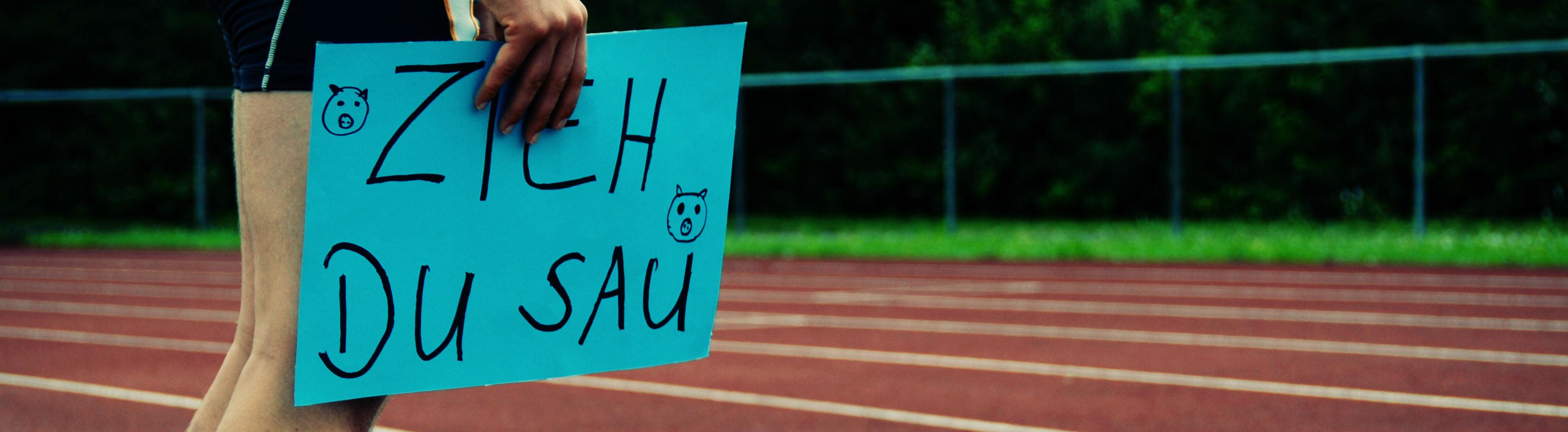 """Ein Läufer hält ein Schild hoch, auf dem """"Zieh, du Sau"""" steht."""