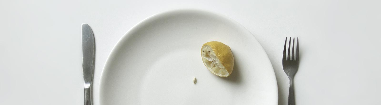 Ein leerer Teller, auf dem nur eine halbe Zitrone liegt, daneben Messer und Gabel