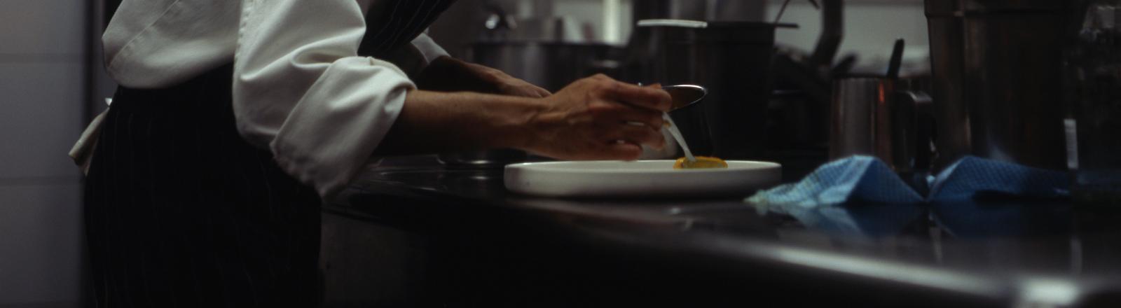 Ein Koch ist in der Großküche über eine Arbeitsfläche gebeugt und befüllt vorsichtig einen Teller