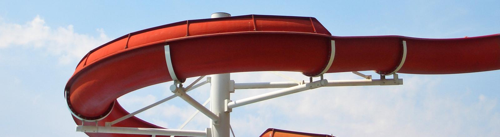Eine rote Wasserrutsche vor blauem Himmel.