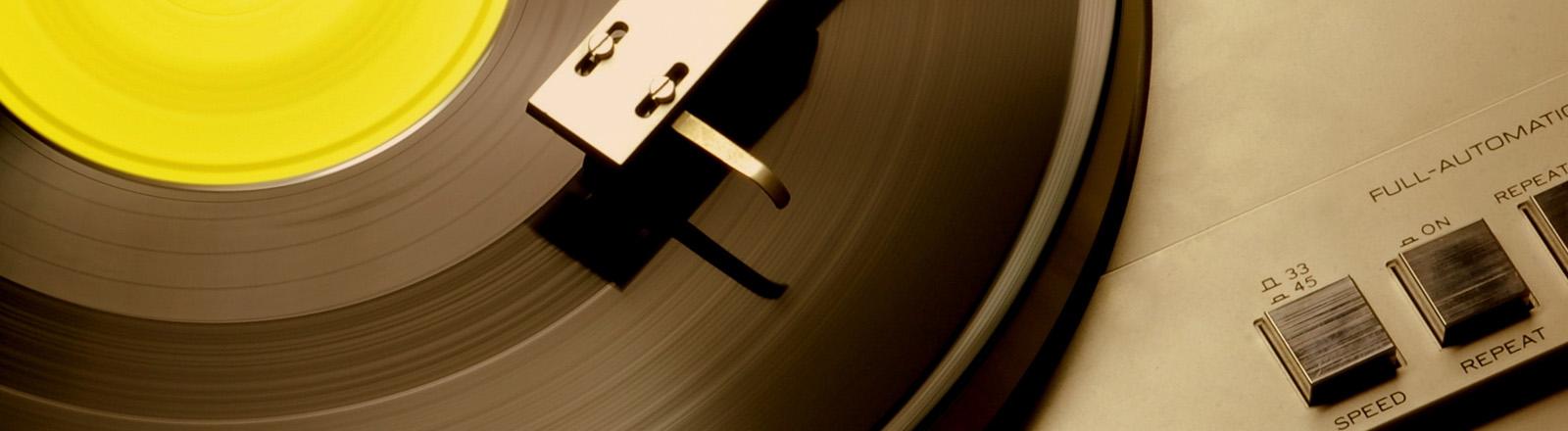 Eine silberne Plattennadel läuft über eine Vinyl.