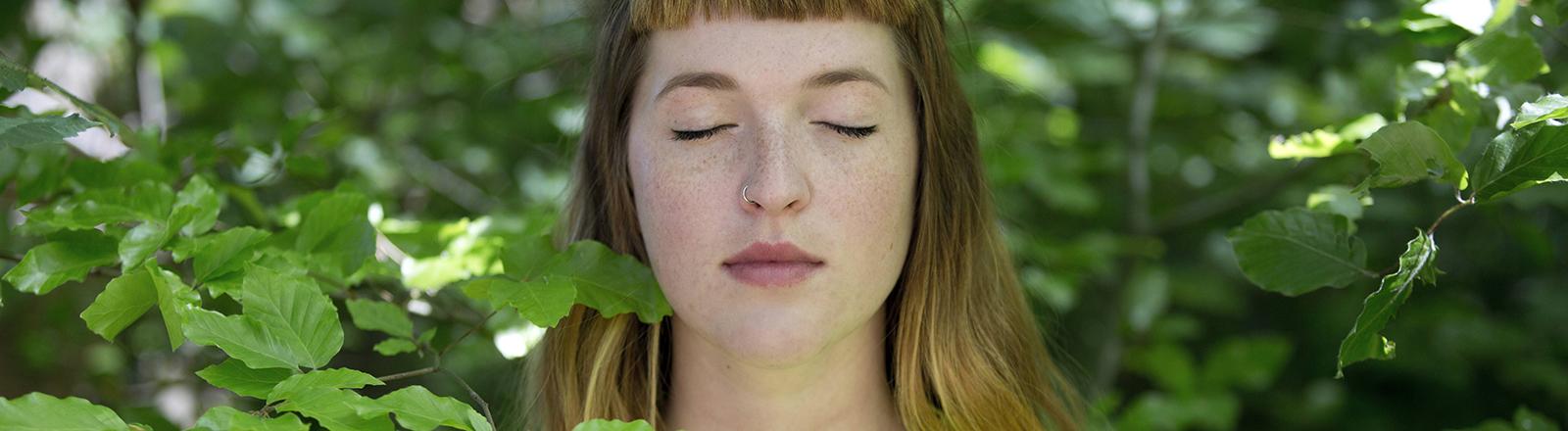 Eine Frau steht mit geschlossenen Augen unter einem Baum.