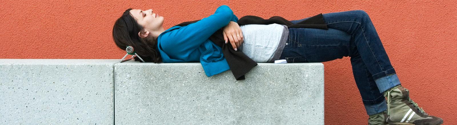 Frau liegt auf einer Betonbank, die Beine am Boden abgestellt, die Augen geschlossen.