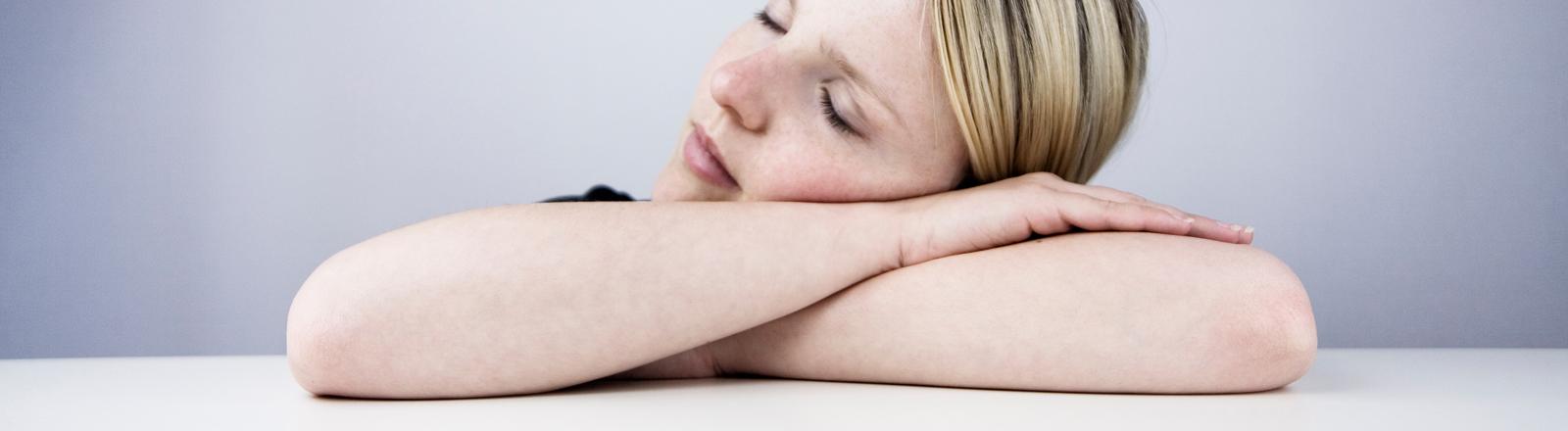 Schlafende Frau,d ie ihren Kopf auf die verschränkten Arme gelegt hat