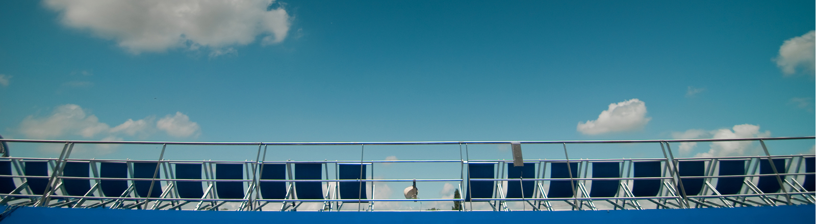 Eine Reihe mit leeren Liegestühlen unter blauem Himmel