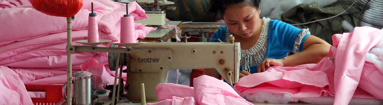 Chinesische Näherin umringt von rosa Stoff