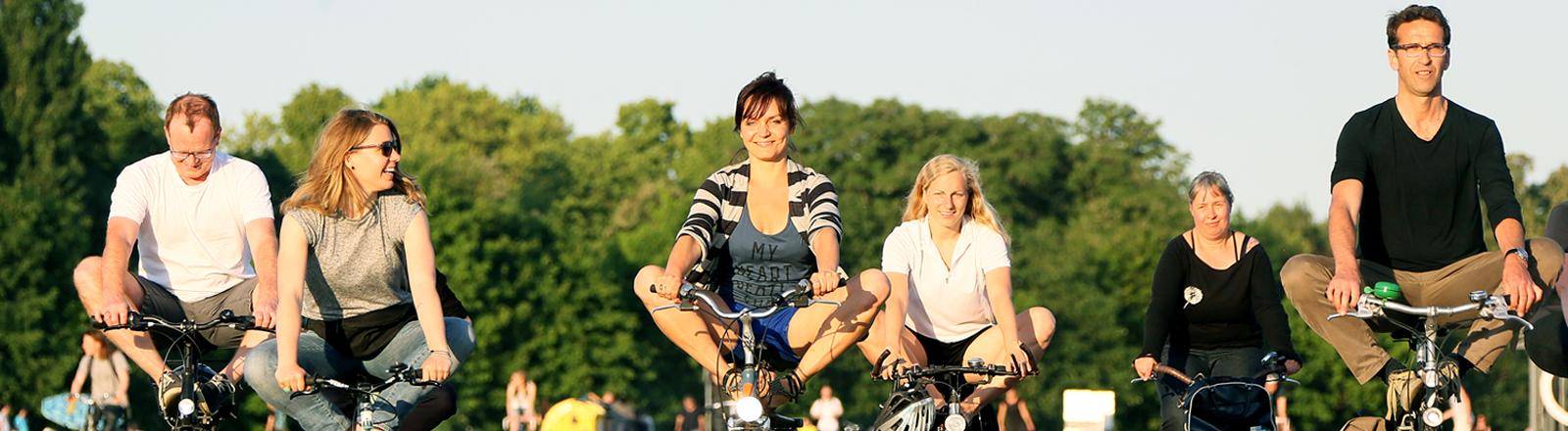 Lachende Menschen machen Yoga-Übungen auf dem Fahrrad