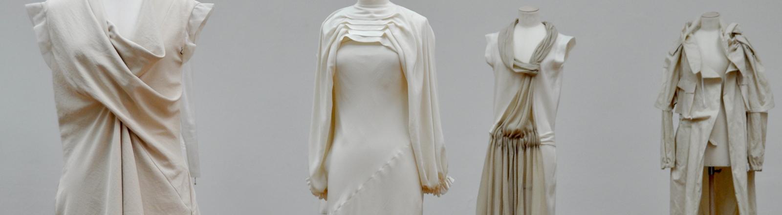 Modepuppen mit Modellen in naturfarbenen Stoffen.