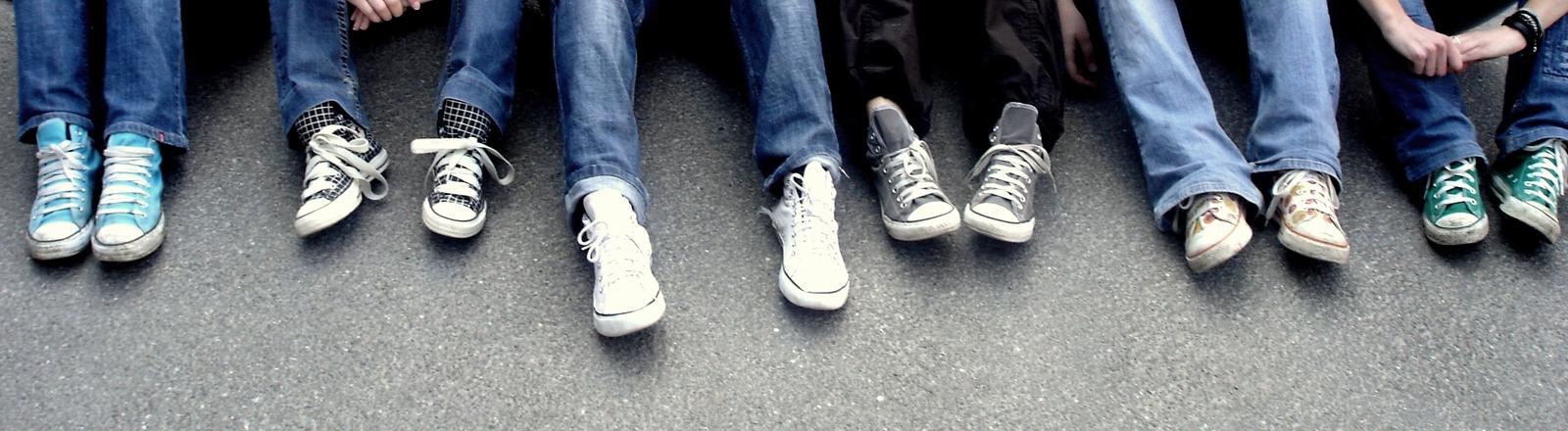 Reihe junger Leute in Jeans und Turnschuhen