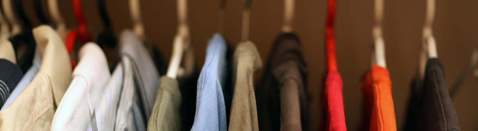 Bügel mit Hemden im Kleiderschrank.