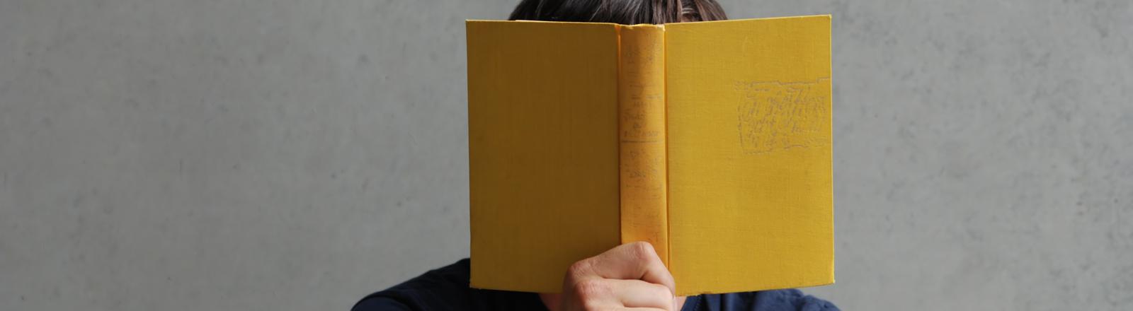 Ein Mann hält ein Buch vor sein Gesicht und liest darin.