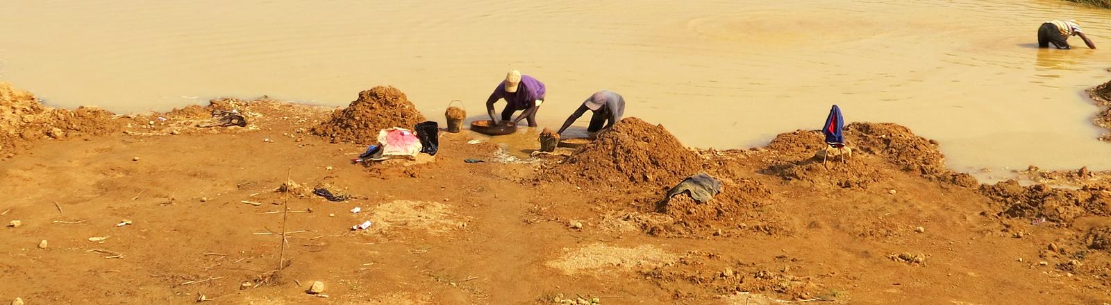 Männer an einem Fluss in Sierra Leone schürfen Diamanten.
