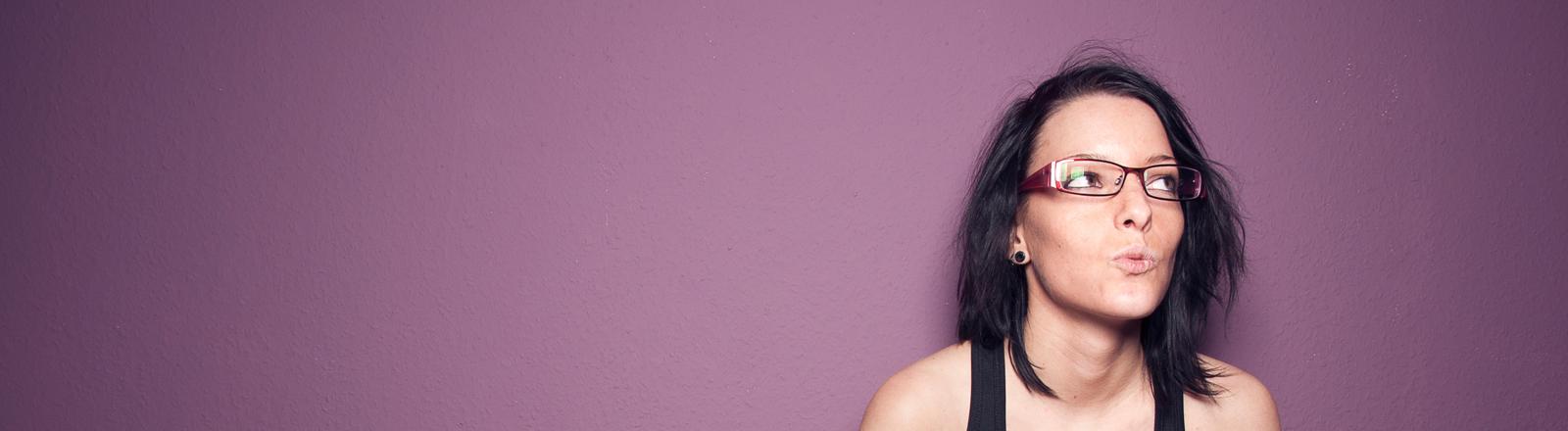 Eine Frau steht vor einer lila Wand und pfeift.