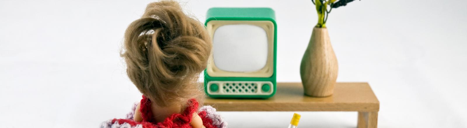 Eine Frau sitzt vor einem Fernseher und schaut Fernsehen.