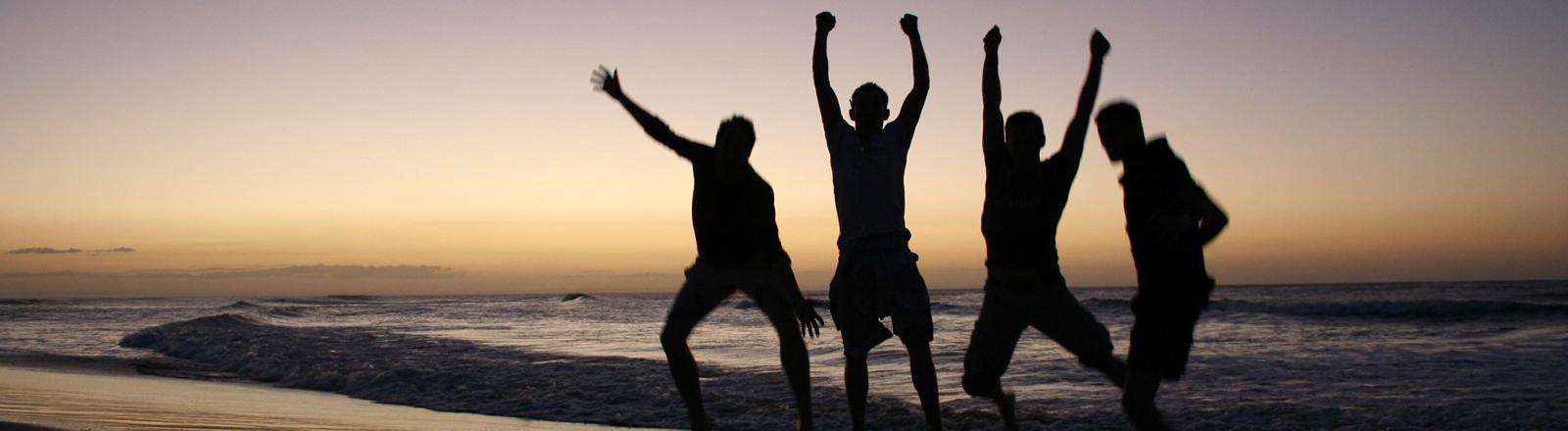Vier Freunde sind am Meer bei Sonnenuntergang und springen alle gleichzeitig in die Luft.