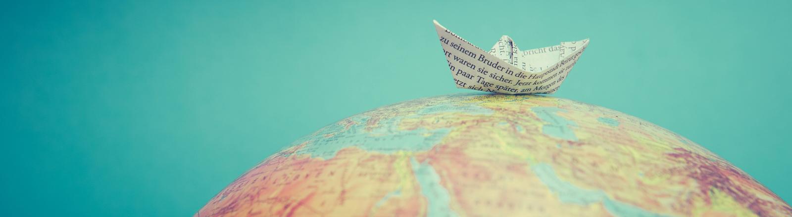 Ein Papierschiffchen auf einer Weltkugel, einem Globus.