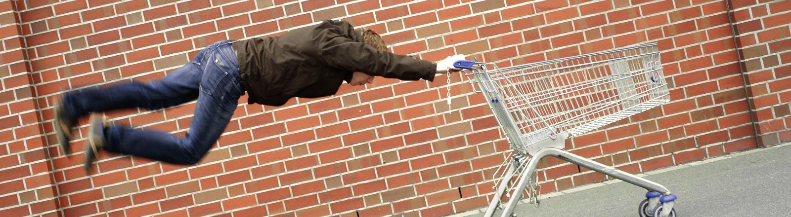 Ein Mann hängt in der Luft hinter einem leeren Einkaufswagen.