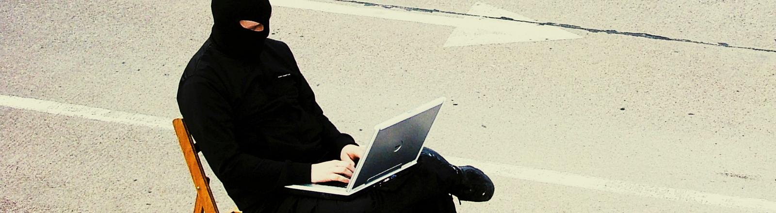 Mann in schwarz gekleidet und mit Sturmmaske, der an einem Laptop arbeitet.